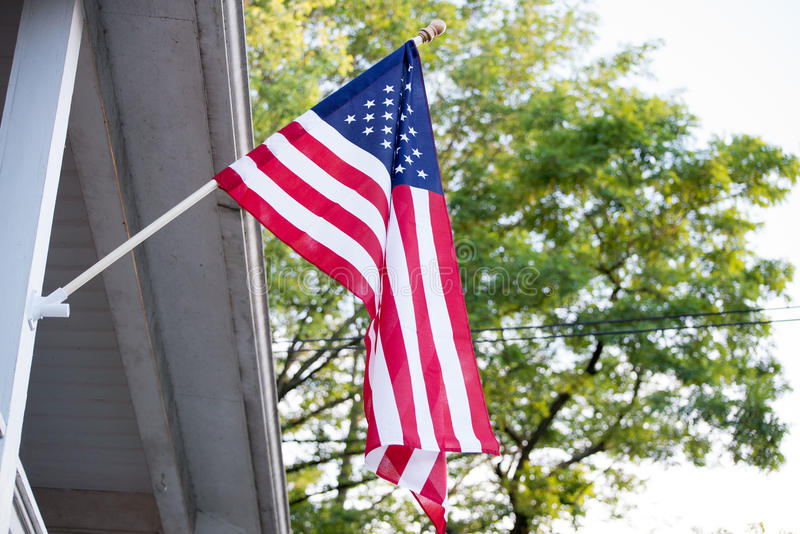 American Flag on house. American Flags sticking out from house stock images
