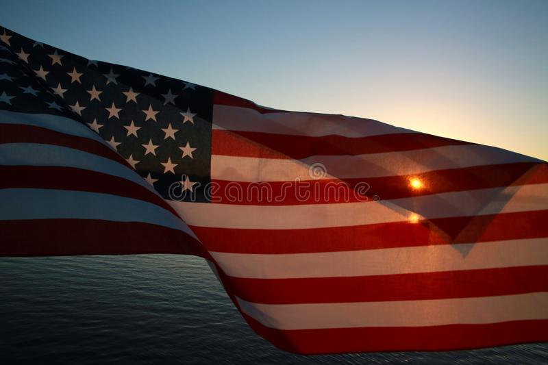 American Flag on Lake at Sunset. An American flag with richly saturated red stripes curls in the breeze as the orange setting sun gleams through a fold against a stock photos