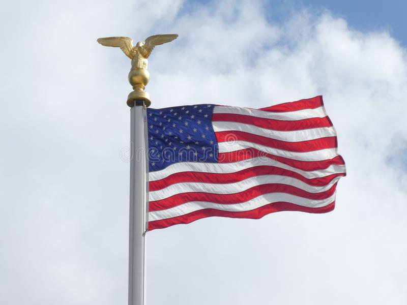 American flag in the light and the wind with a cloudy sky in the background. The flag of the United States is nicknamed Stars and Stripes or The Star-Spangled stock photo