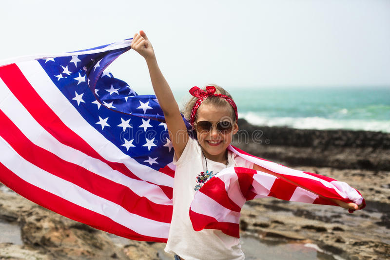 American Flag. Little smiling patriotic girl with long blond hair, red head band bandana and sunglasses holding an  waving in the wind on the ocean beach royalty free stock photo