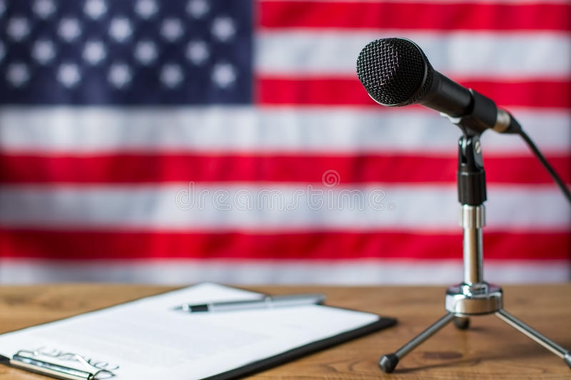 American flag, microphone and paper. Clipboard and microphone beside banner. TV show scenario on table. Notes of news host royalty free stock images