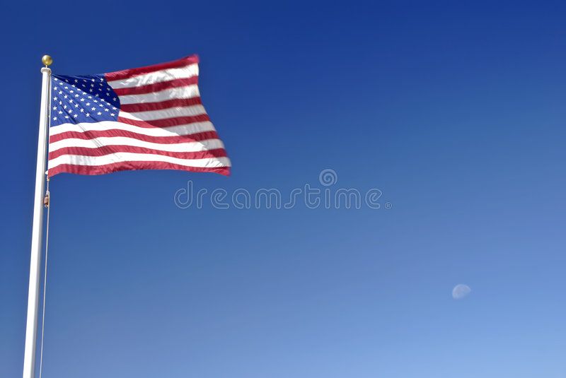American Flag & Moon. American flag billowing against a deep blue clear sky with the moon in the background stock image