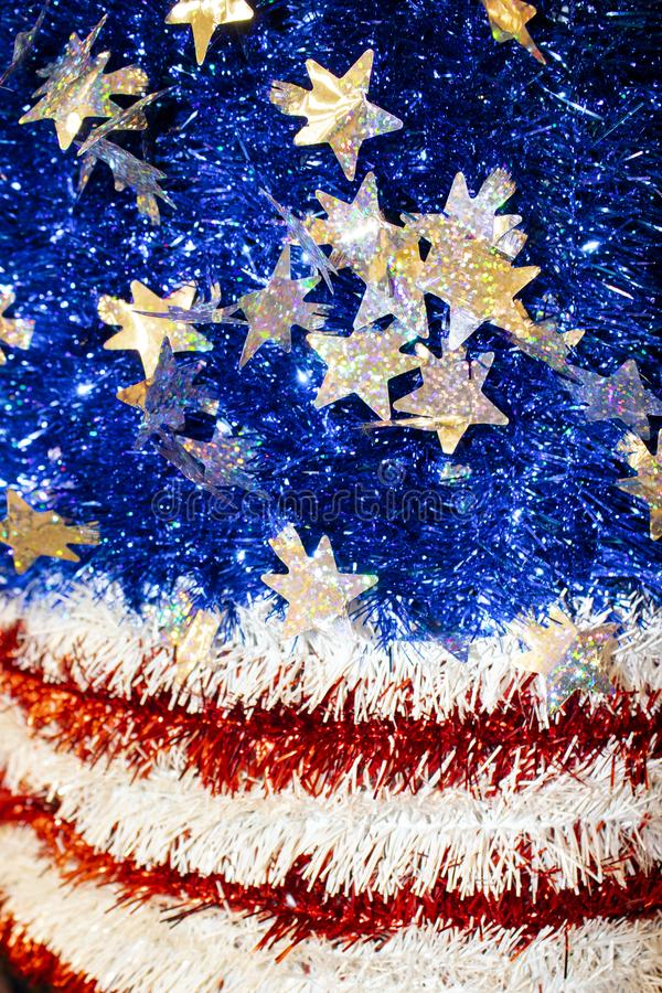 American Flag motif in red white and blue tinsel with sparkly stars with a bokeh blur effect - background or design element. An American Flag motif in red white royalty free stock image