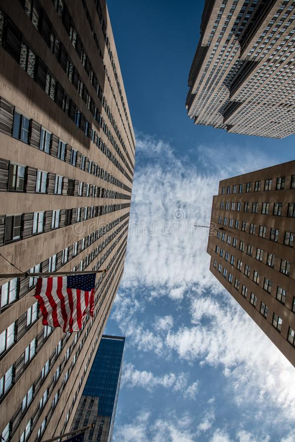 An American flag in motion at the Rockefeller Center. American flag by the Rockefeller Center  in the heart of Manhattan stock photo