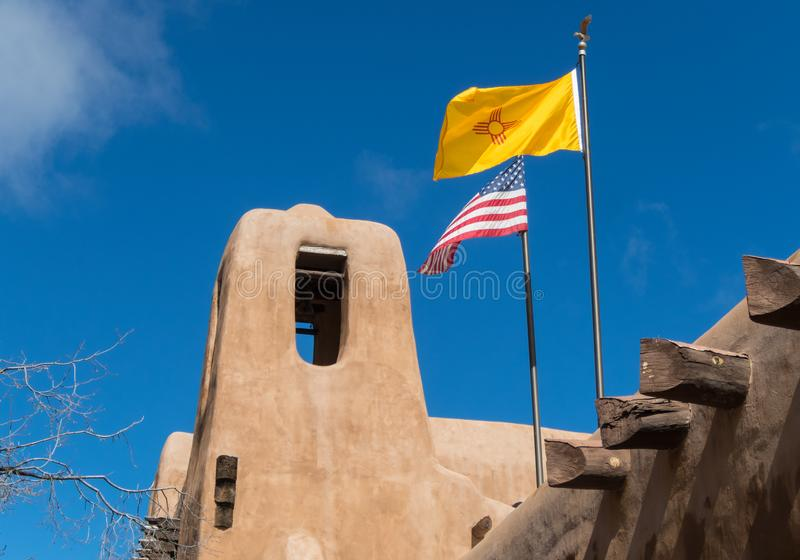 American flag, New Mexico flag. American flag and New Mexico flag fly above mission style building, Santa Fe, New Mexico royalty free stock images