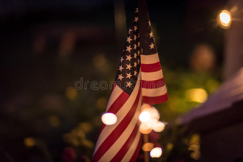 American flag at night with sparklers and bokeh lights. US flag on a summer evening with white bokeh circles around it stock photos