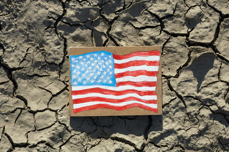 American Flag painted on paper lying on cracked earth stock images