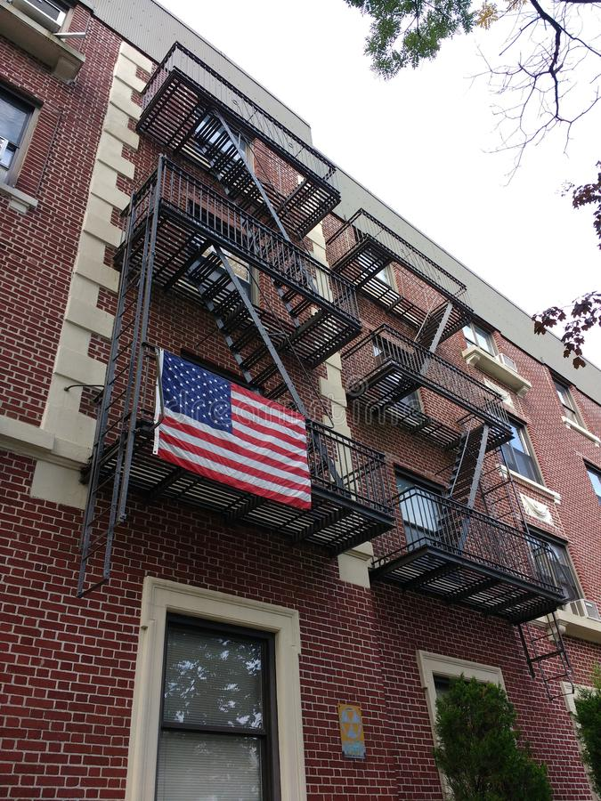 American Flag on a Brooklyn Fire Escape, USA. An American flag patriotically displayed from the fire escape of an apartment building in Bay Ridge, Brooklyn. This royalty free stock image