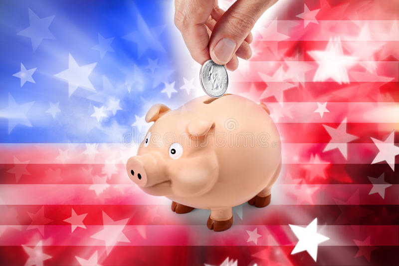 American Flag Piggy Bank Money. A mans hand holding an American quarter coin with an abstract American flag background stock photos