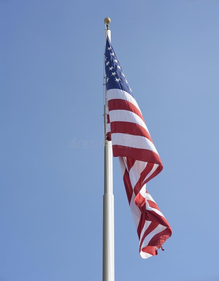 American flag. On the pole against blue sky stock photo