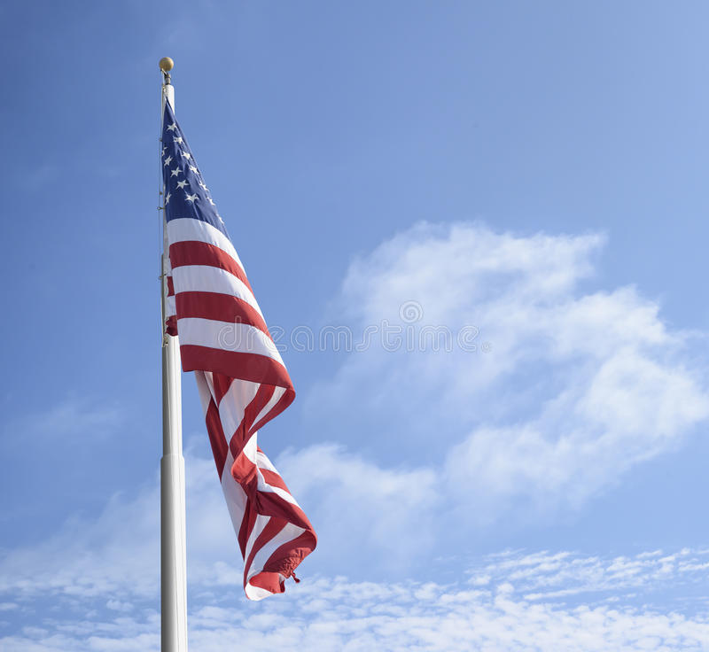 American flag. On the pole against blue sky and clouds stock photo
