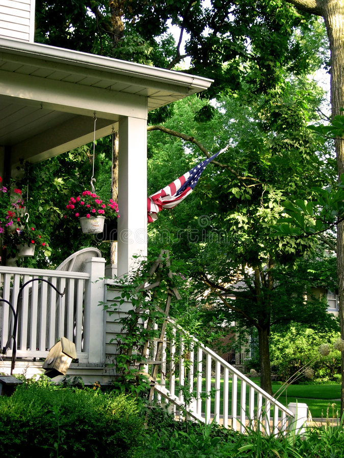 American flag on porch. Of Victorian home, with flowers and trees royalty free stock photos