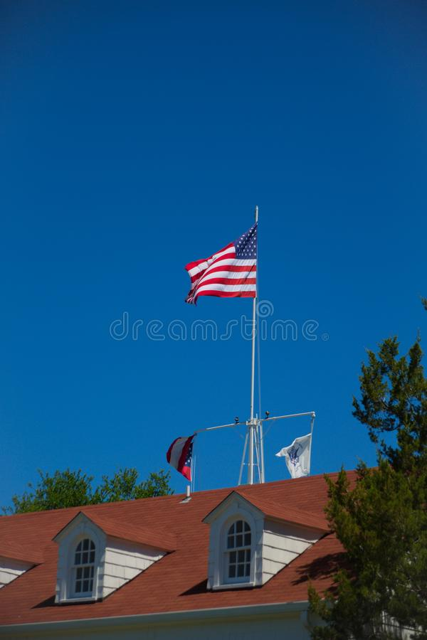 American Flag on Red Roof. The American flag flying against a clear blue sky over a red roof with dormers stock images
