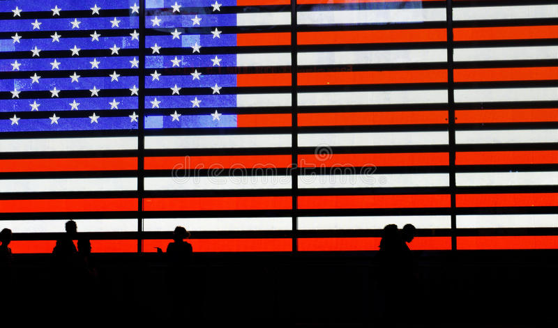 American Flag. Silhouettes of several people passing by a neon American Flag in Times Square, New York stock photo