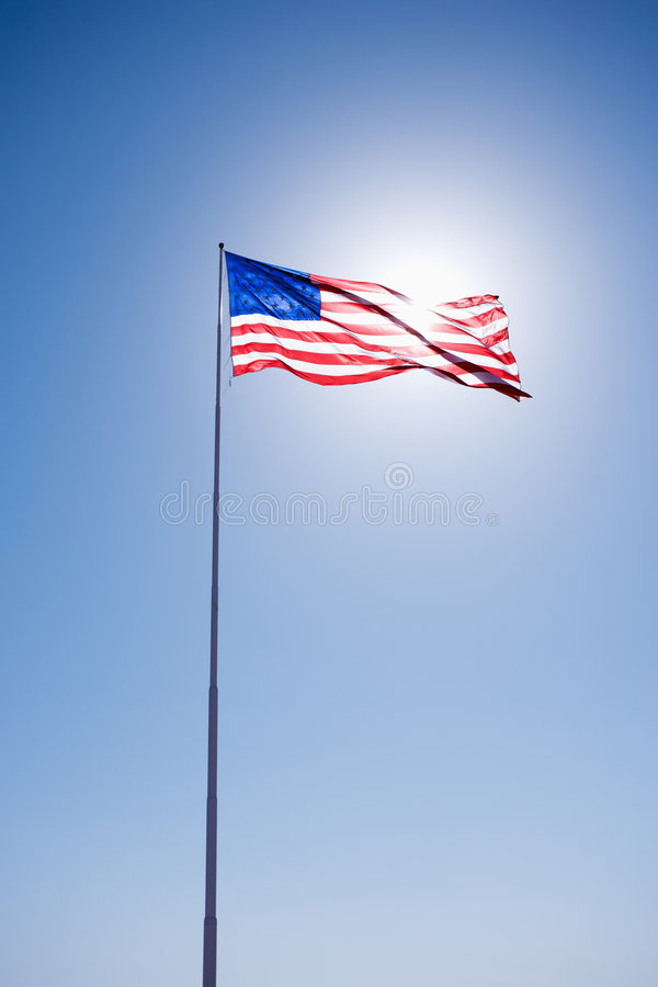 American flag in sky. American flag blowing in clear blue sky royalty free stock image