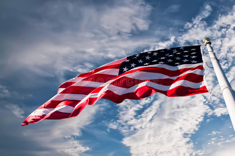 American flag in the sky. American flag waving against blue sky royalty free stock images
