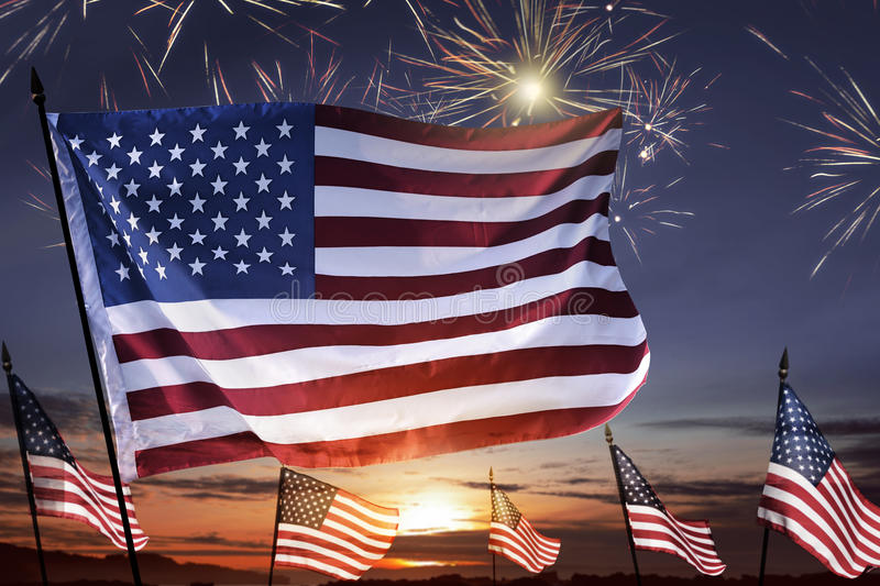 American flag on the sky waving celebrating 4th of July. With fireworks background royalty free stock images