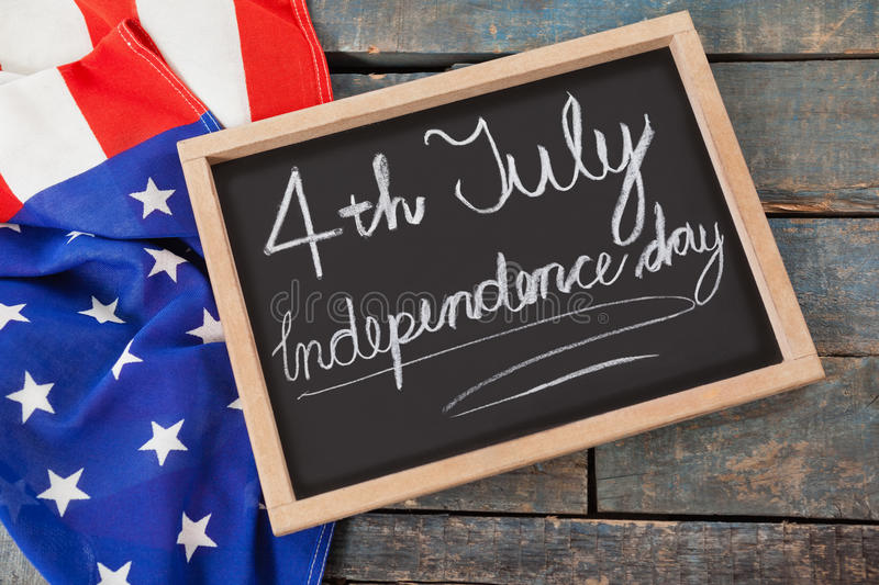 American flag and slate with text 4th july independence day. Close-up of American flag and slate with text 4th july independence day royalty free stock photo