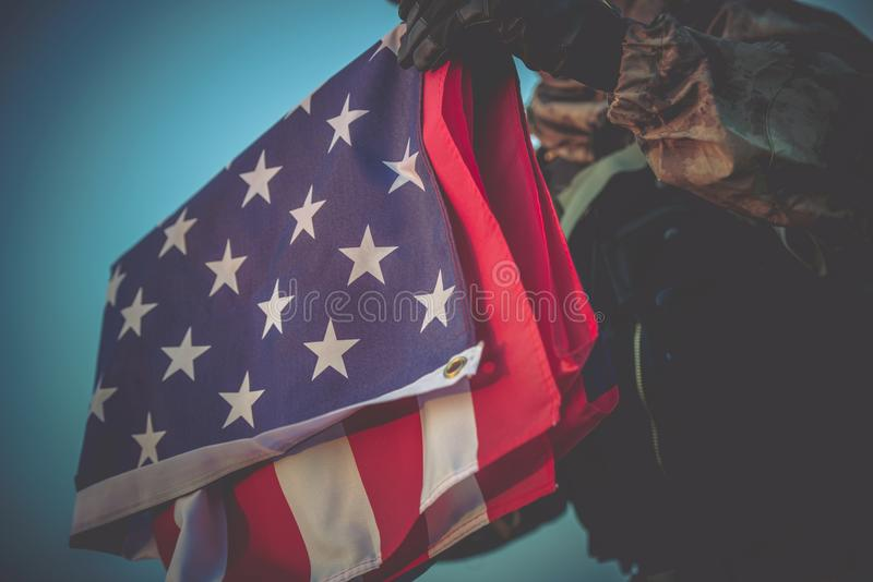 American Flag in Soldier Hands. Folded American Flag in Soldier Hands Closeup Photo stock photography