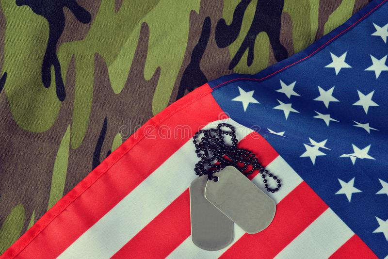 American flag and soldiers badges on camouflage fabric. stock photo