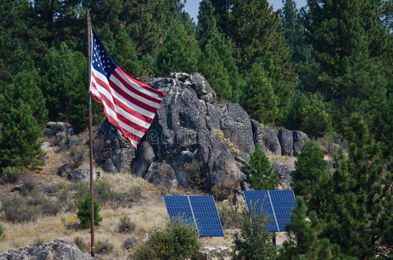 American Flag Standing in the Wilderness Beside Two Solar Panels royalty free stock images