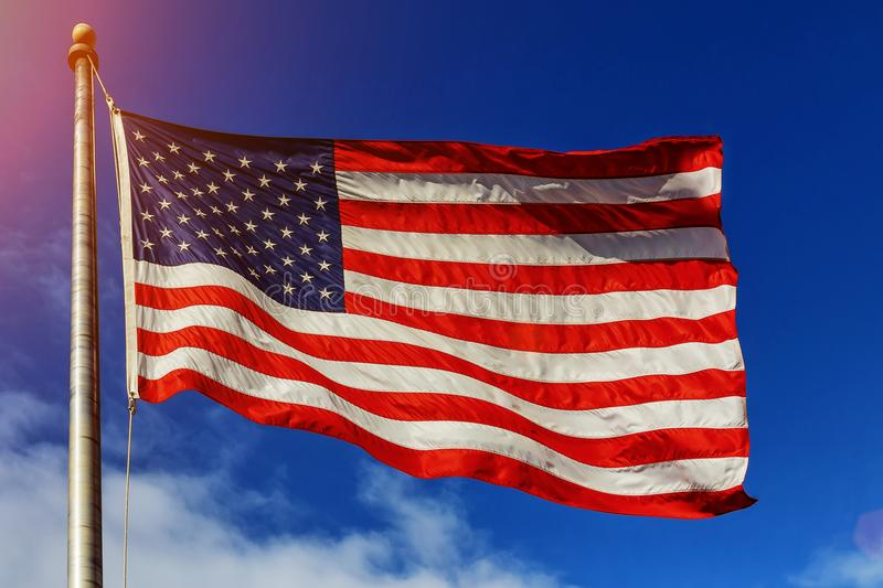 American flag -star and stripes floating over a cloudy blue sky. American flag - star and stripes floating over a cloudy blue sky royalty free stock photo
