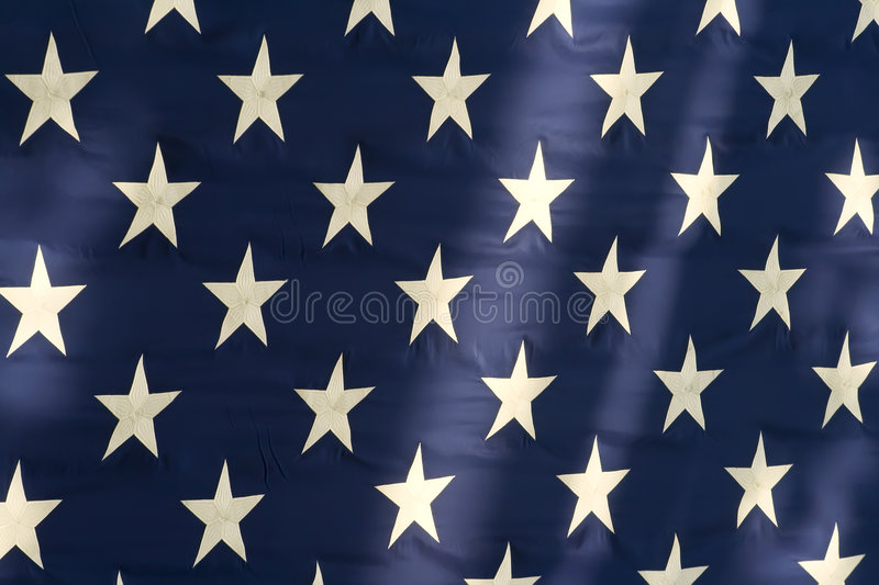 American Flag Stars. Closeup view of stars on American flag with shadows and sunlight royalty free stock photography