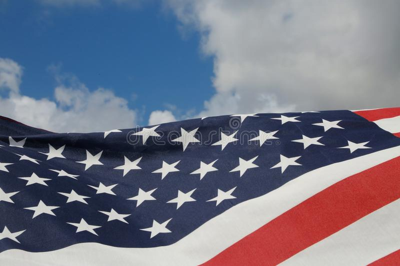 American Flag. The stars and stripes of the American flag wave and flutter patriotically in the morning sun stock photo