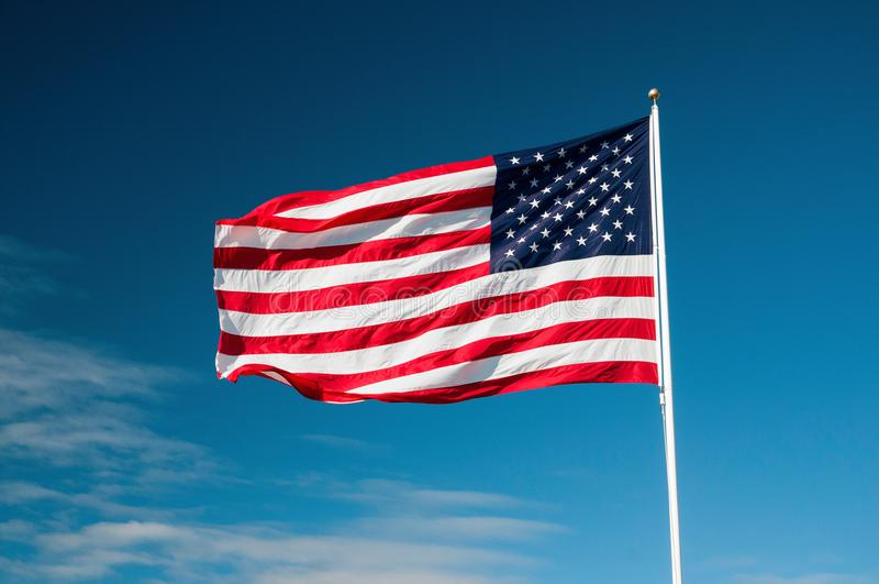 American Flag on a sunny day. American Flag blowing in the wind with blue sky background royalty free stock photos
