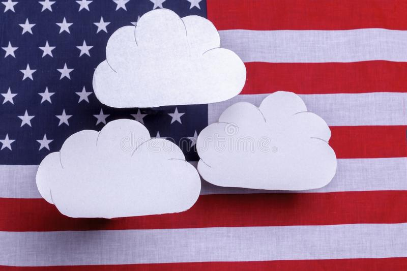 American flag with three white clouds floating above. American flag star spangled banner with three white clouds floating over the flag. Red white and blue old royalty free stock image