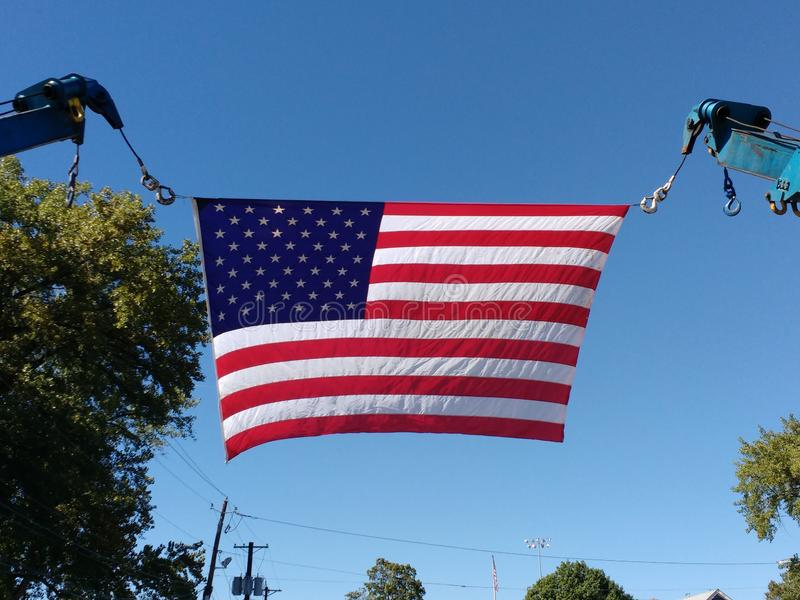 American Flag Between Two Boom Crane Hooks. A large American flag is flown between two tow truck boom crane hooks stock photography