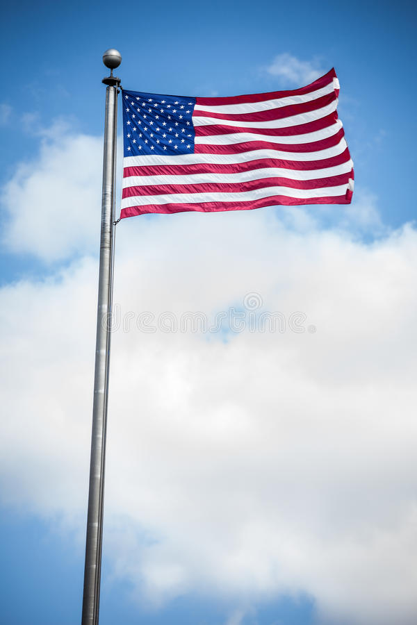 American Flag. Vertical view of an American flag blowing in the wind against the clouds stock image