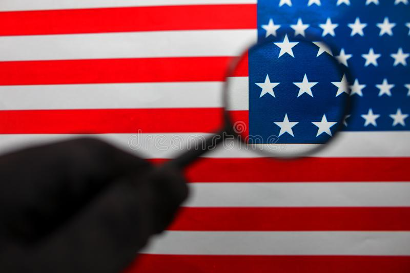 The American flag is viewed through a magnifying glass. Spies and surveillance USA concept. Control of the state of the United. States. War Terrorism Theft stock photos