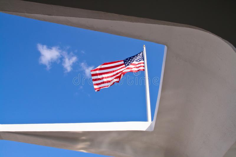 American Flag viewed from the USS Arizona Memorial. Set against a blue sky stock photography