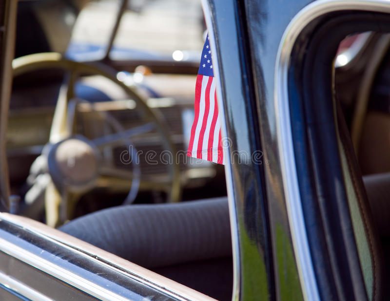 American Flag In A Vintage Car. A small American flag peeks out of the window of an antique, beautifully restored American-made sedan royalty free stock photos
