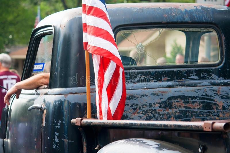American Flag on Vintage Pickup Truck. An American flag is attached to the back of an old, beat up pickup truck driving in an Independence Day Parade stock image