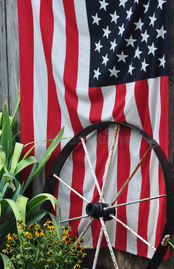 The American Flag and Wagon Wheel in a garden setting stock image