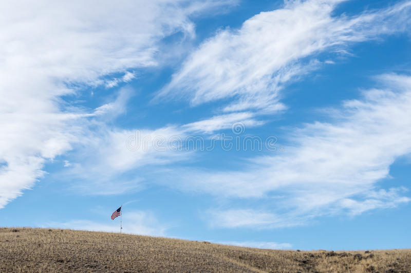 American flag. An American flag waves under a blue wyoming sky stock photography