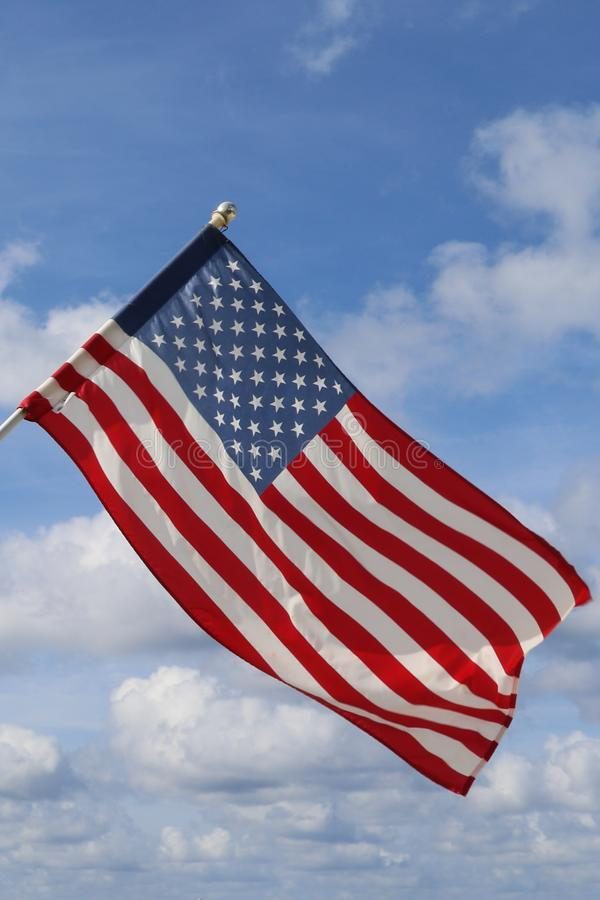Waving USA flag in blue and cloudy sky. American symbol of fourth of July Independence Day royalty free stock photos