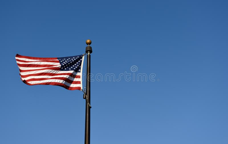 American flag waving in the breeze with a clear blue sky. Background in the USA royalty free stock photography