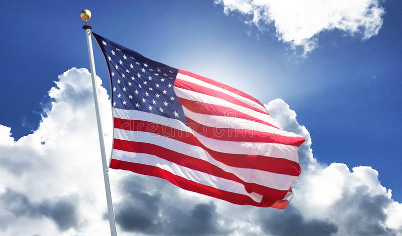 American Flag waving in bright blue sky stock photography