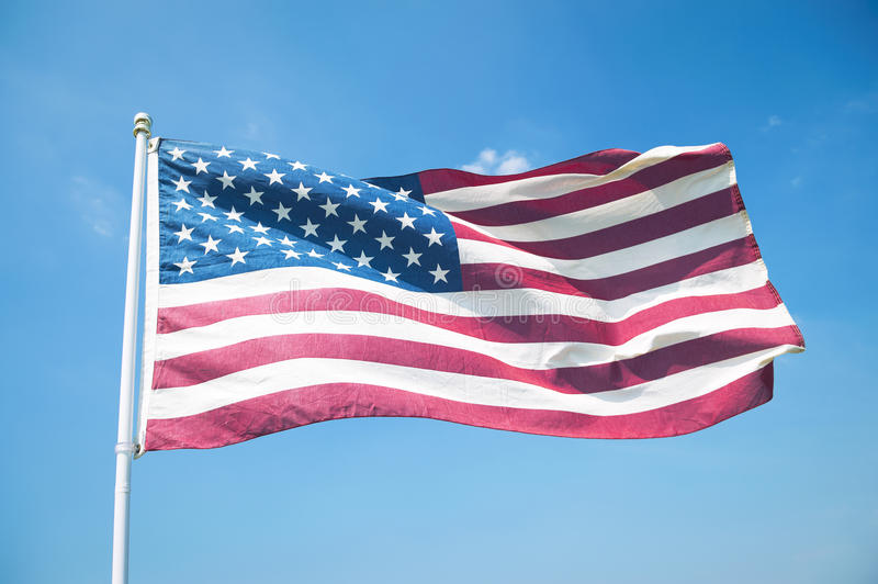 American Flag Waving in Bright Blue Sky. The red, white, and blue stars and stripes of an American flag waving in bright blue sky stock photos
