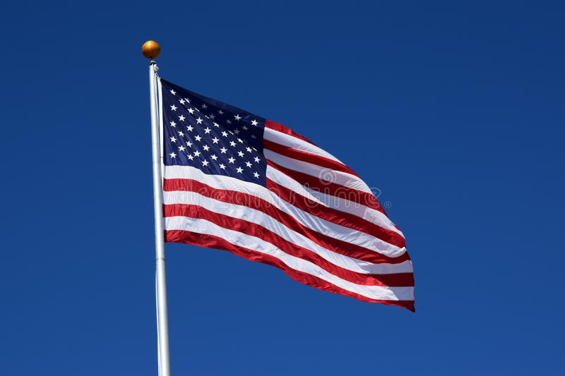 American flag. Waving in the clear blue sky stock photography