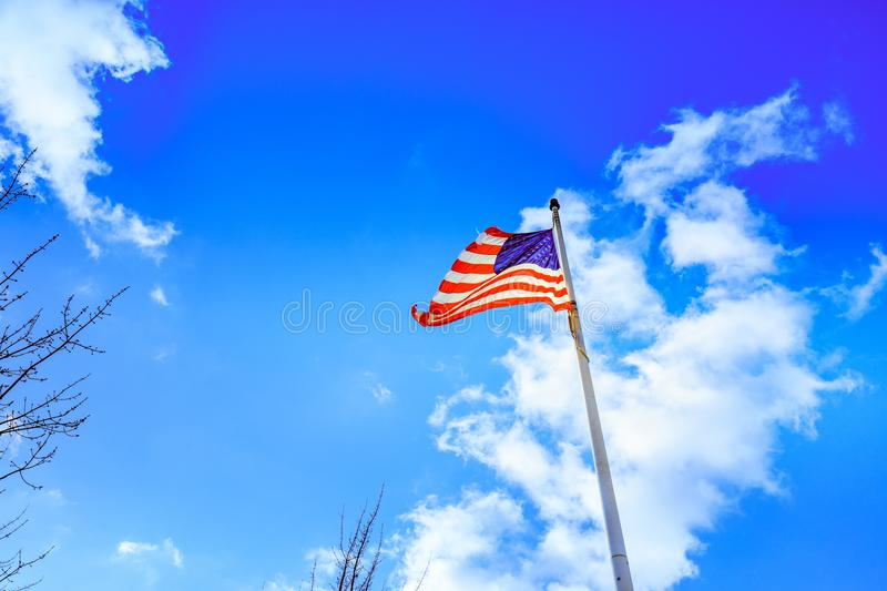 American flag waving under a blue sky with clouds royalty free stock photography