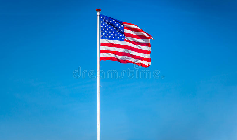 American flag waving in the wind, USA. American flag waving in the wind on blue sky in the USA royalty free stock photography