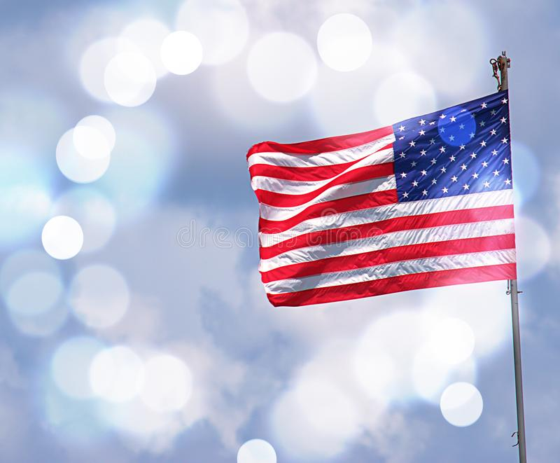 American Flag With White Bokeh In Background. American Flag flying in the wind with white bokeh in the background royalty free stock image