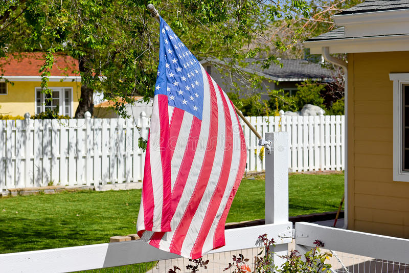 American Flag Wooden Fence. American flag hangs off a pole attached to a wooden fence royalty free stock photos
