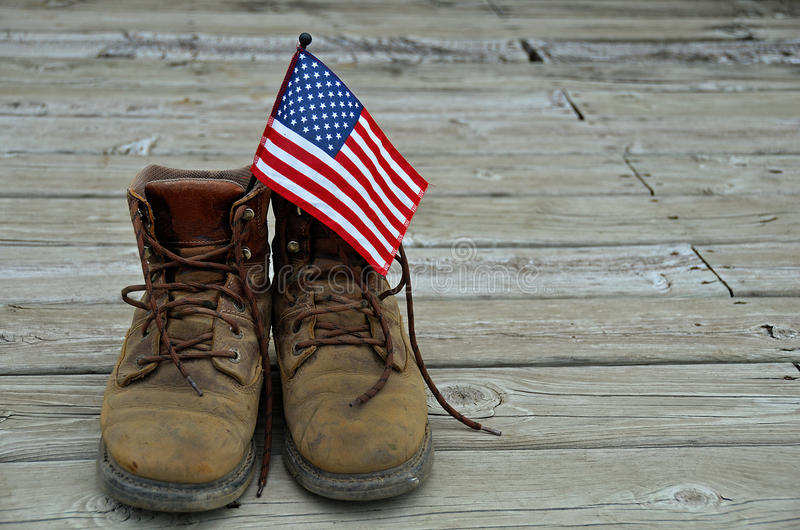 American flag in work boots. Brown work boots with American flag on a wooden deck stock images