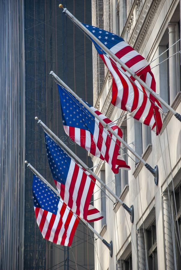 4 american flags hanging on facade of a skyscraper in Manhattan, New York City royalty free stock photography
