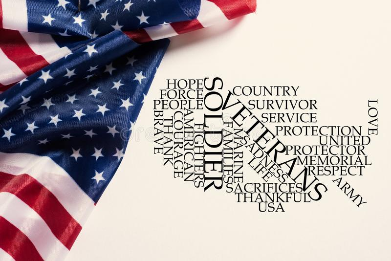 American flags and tag cloud honoring the veterans. Some american flags and a tag cloud, in the shape of the map of the United States, with words to honor the stock images